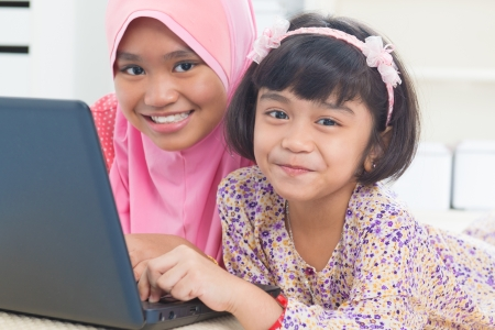 Southeast Asian children surfing internet at home. Malay Muslim girls photo
