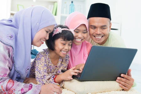Southeast Asian family browsing internet at home. Lying on floor using computer laptop. Stock Photo - 16856960