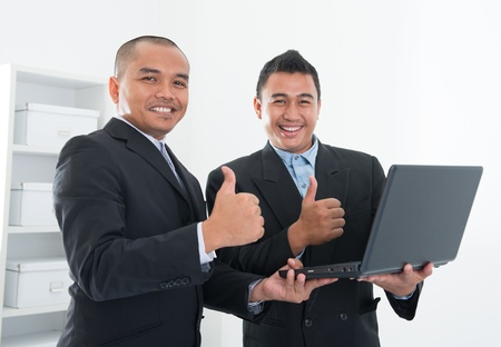 logon: Southeast Asian business people thumbs up, holding notebook in workplace