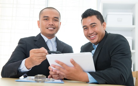 logon: Southeast Asian business people on ebusiness activity, sitting in office.