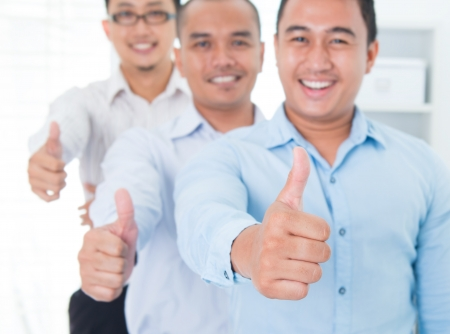 malaysian people: Thumbs up Southeast Asian business group standing in office