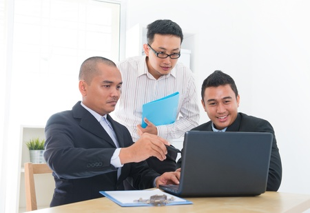 Southeast Asian business team discuss in office photo