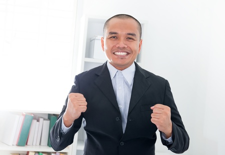 filipino adult: Excited Southeast Asian businessman smiling in office Stock Photo