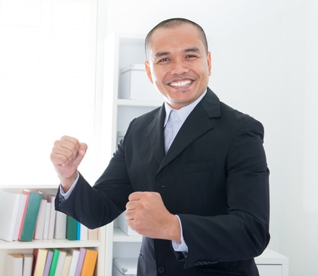 filipino people: Cheerful Southeast Asian businessman smiling in office