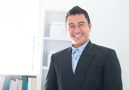 Attractive Southeast Asian executive standing in office photo