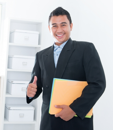filipino adult: Thumb up Southeast Asian executive standing in office