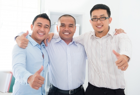 Thumbs up Southeast Asian businessmen standing in office Imagens