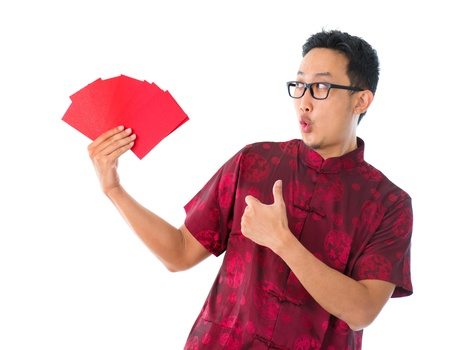 ang: Thumb up Asian Chinese man showing many red packets  ang pow, isolated on white background