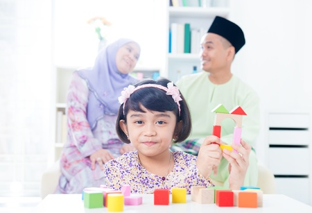 Muslim child building wooden house. Southeast Asian girl playing woodblock house at home. photo