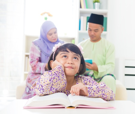 Southeast Asian family reading book at home. Muslim family living lifestyle. photo