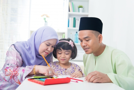Muslim family drawing picture at home. Southeast Asian family lifestyle. photo