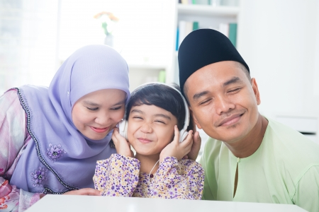 Southeast Asian family listen mp3, sharing headphone. Muslim family living lifestyle photo