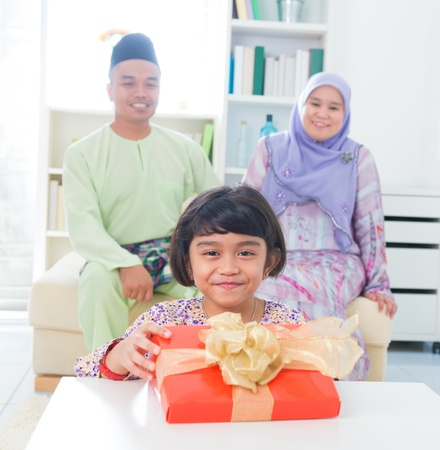 Southeast Asian girl with birthday present. Muslim family living lifestyle. Stock Photo - 17056480