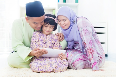 Southeast Asian family using computer internet at home. Muslim family living lifestyle photo