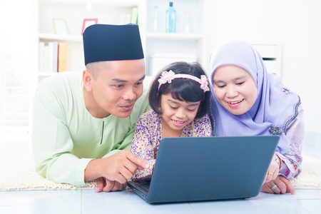 Southeast Asian family browsing internet at home. Muslim family living lifestyle Stock Photo - 17056458