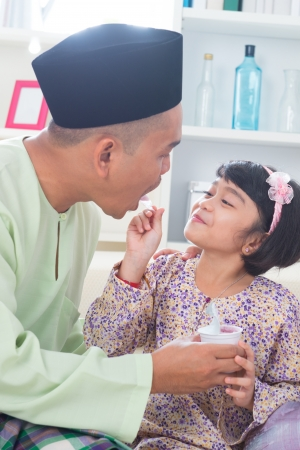 Cute Southeast Asian girl feeding yogurt to her father. Malay Muslim family lifestyle photo