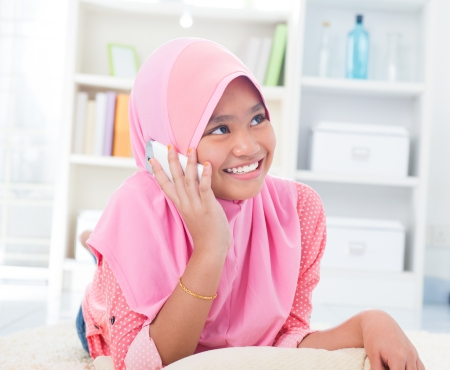 Southeast Asian teenager on the phone at home. Muslim teen girl living lifestyle. Stock Photo - 17056488