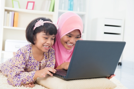Southeast Asian females surfing internet at home. Malay Muslim girls. photo