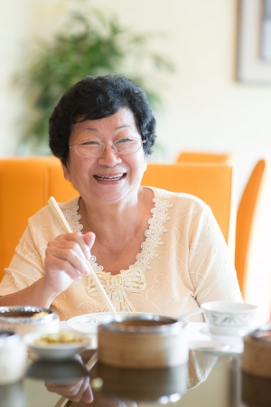Happy 60s Senior Asian Woman dining indoors photo