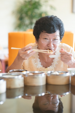 Happy 60s Senior Asian Woman dining at restaurant photo