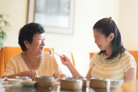 teatime: Asian Chinese adult daughter feeding her senior parent food Stock Photo