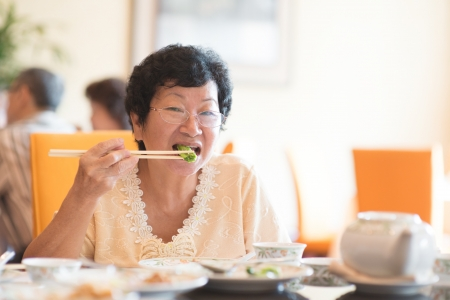 candid: Happy 60s Senior Asian Woman eating vegetable at restaurant