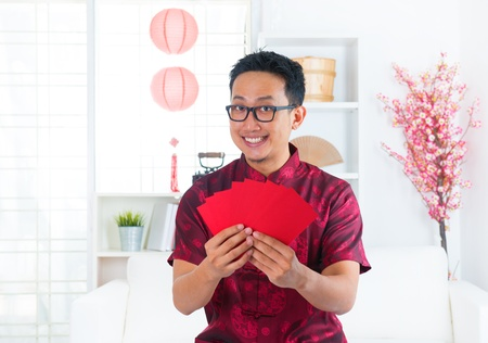 Southeast Asian Chinese man showing many red packets / ang pow indoors Stock Photo - 17056486