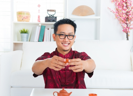 Southeast Asian Chinese man holding teacup indoors photo