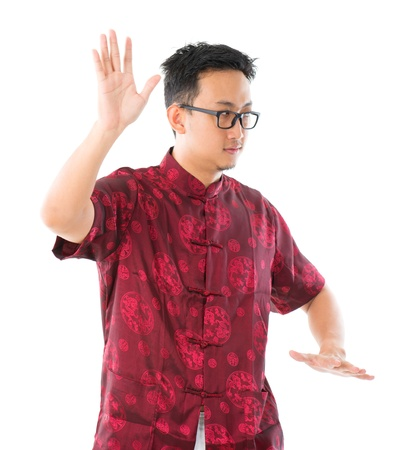 Southeast Asian Chinese male practicing tai chi, isolated on white background photo