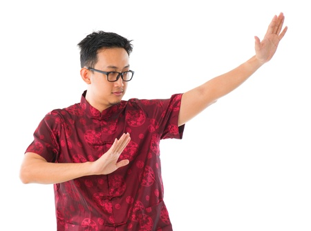 Southeast Asian Chinese man practicing tai chi, isolated on white background photo