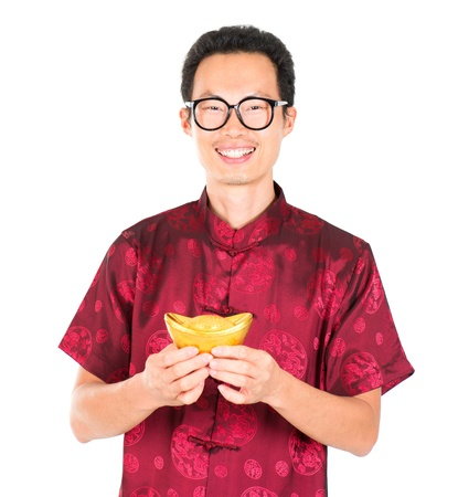 China man in traditional Chinese Tang suit greeting, holding a gold ingot isolated on white background photo