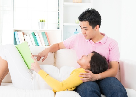 Asian pregnant woman reading book together with husband photo