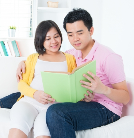 Asian couple reading book together, sitting on sofa photo