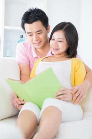 Asian couple reading book on sofa happily photo