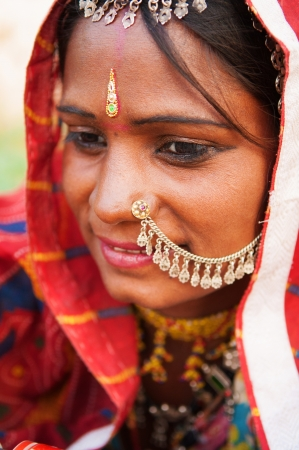 Young Traditional Indian woman in sari costume covered her head with veil, India photo
