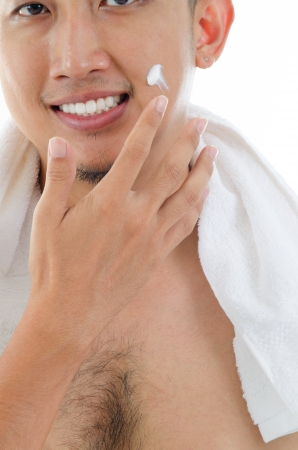 asian man face: Asian man skin care, putting on cream lotion on face Stock Photo