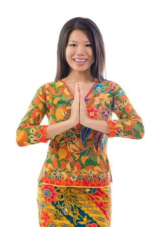 folded hands: Southeast Asian female in a traditional greeting gesture, isolated white background