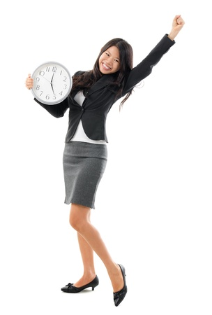 Excited Office Lady off work at 5pm. Full body Southeast Asian Chinese Business woman holding a wall clock standing isolated white background. photo