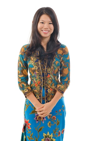Southeast Asian woman in traditional batik kebaya clothing, isolated white background photo