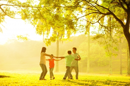 Happy Asian family playing together at outdoor park photo