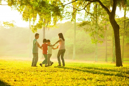 freedom park: Happy asian family playing on the field during sunrise. People running in circle under the tree at outdoor green park. Stock Photo
