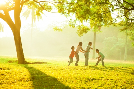 Asian family outdoor quality time enjoyment, asian people playing during beautiful sunrise photo