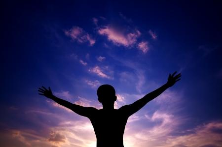manos levantadas al cielo: Oa contraluz la silueta de brazos abiertos hombre asi�tico elev� hacia el cielo en la puesta del sol
