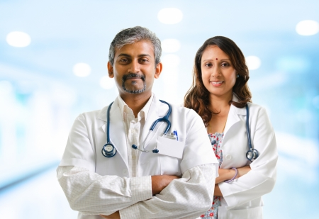 Indian doctors or medical tem crossed arms standing, hospital background