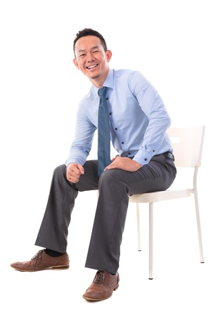 Full body Asian business man sitting on a chair over white background photo