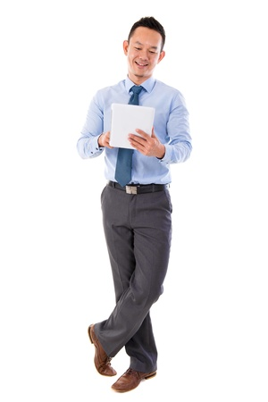 Full body Asian businessman using tablet-pc standing isolated white background photo