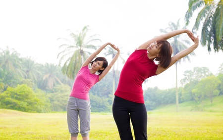 warmup: Two Asian girls stretching outdoor green park Stock Photo