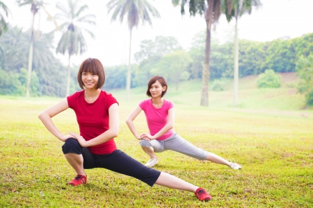 Two cheerful Asian girls stretching outdoor green park photo