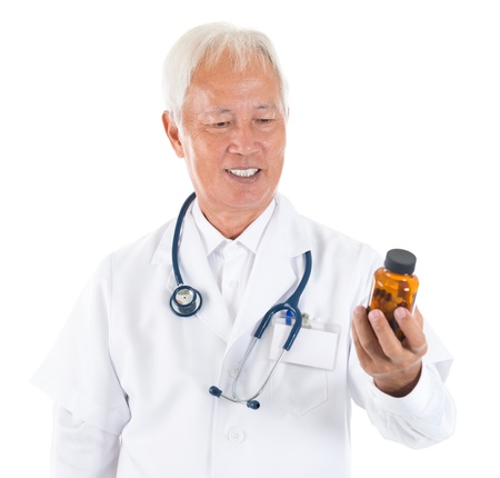 Asian senior doctor holding a bottle of pills, smiling isolated white background photo