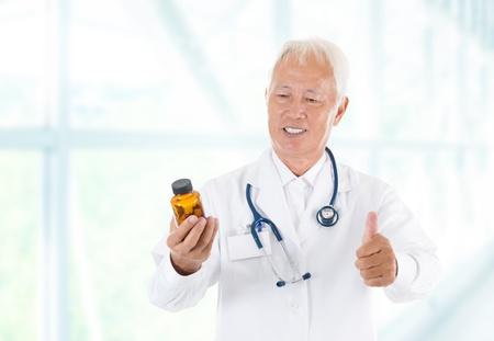 Asian senior doctor holding a bottle of pills, thumb up isolated white background photo